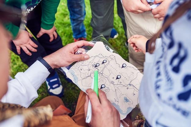O animador, junto com as crianças, está tentando resolver o cartão das crianças