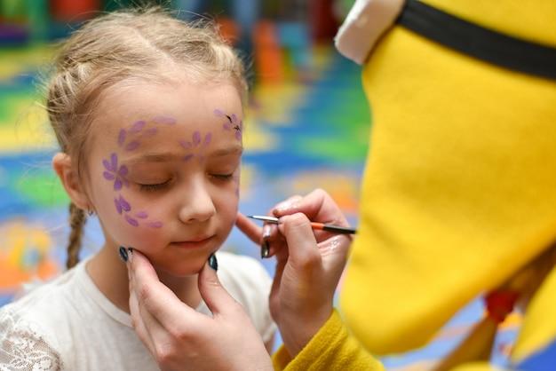 O animador pinta o rosto da criança
