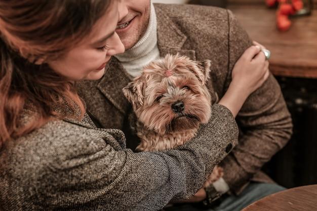 O animal de estimação favorito. homem e mulher abraçando seu cachorro
