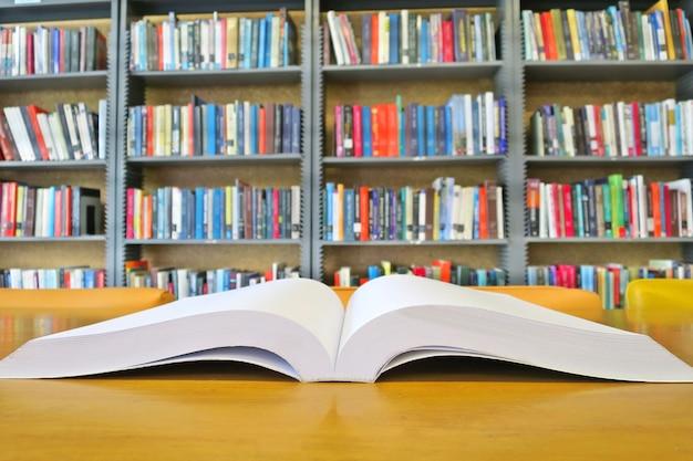 O antigo livro aberto na mesa de madeira na biblioteca