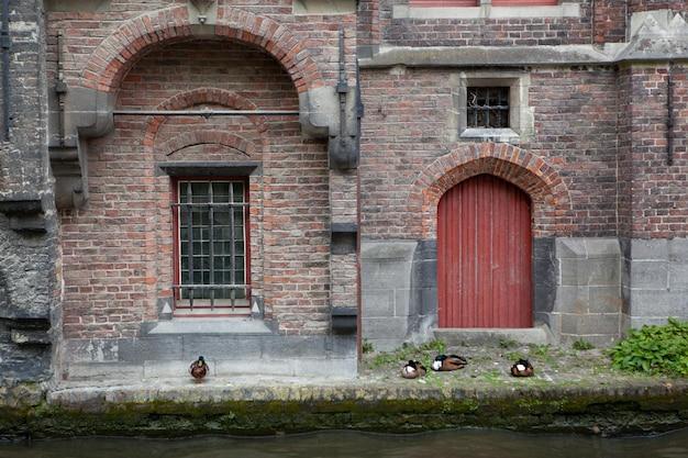 O antigo prédio com a porta vermelha e uma janela no canal de água