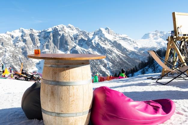 O aperol da caneca está na tabela de um café ao ar livre em uma estância de esqui.