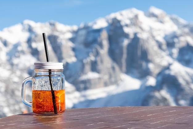 O aperol da caneca está na tabela de um café da rua contra o contexto das montanhas.