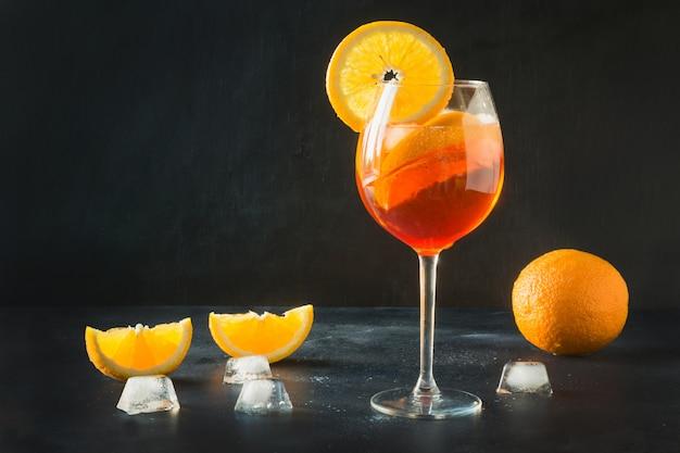 O aperol italiano clássico spritz o cocktail na obscuridade.