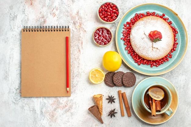 O apetitoso bolo uma xícara de chá e o bolo ao lado do caderno e lápis