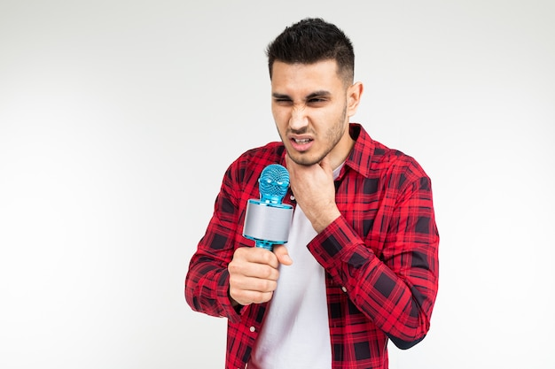 O apresentador masculino com um microfone nas mãos tem uma dor de garganta em um fundo branco e isolado do estúdio