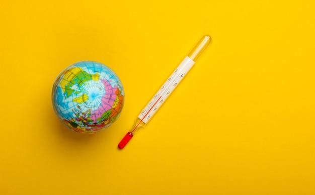 O aquecimento global ainda vida. globo e termômetro em uma parede amarela questões climáticas globais. conceito ecológico
