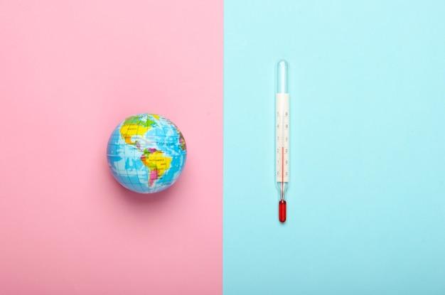 O aquecimento global ainda vida. globo e termômetro na parede azul rosa questões climáticas globais. conceito ecológico. vista do topo