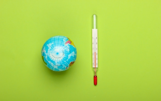 O aquecimento global ainda vida. globo e termômetro na parede verde questões climáticas globais. conceito ecológico