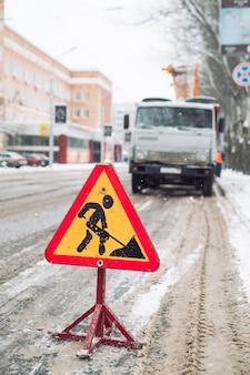 O arado de neve remove a neve da rua da cidade. sinal de estrada de aviso. trabalho de soprador de neve de veículo de serviço de inverno. limpeza de estradas congeladas de neve.