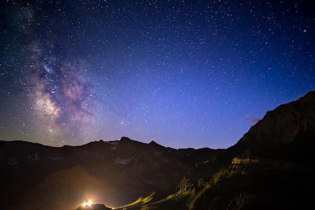 O arco da via látea e o céu estrelado capturaram na alta altitude no verão nos alpes italianos, província de torino.