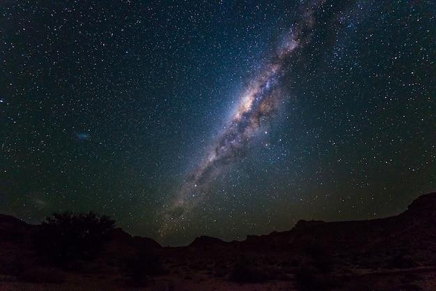 O arco da via látea, protagoniza no céu, o deserto de namib em namíbia, áfrica. a pequena nuvem de magalhães no lado esquerdo.