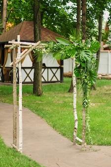 O arco de casamento é decorado com folhas verdes