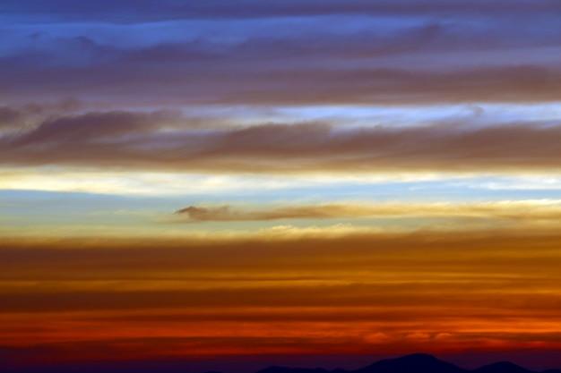O arco-íris e o céu azul vermelho amarelo laranja nuvem no pôr do sol na montanha