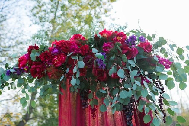 O arco para a cerimônia de casamento, decorado com flores de tecido e folhagens, fica em uma floresta de pinheiros