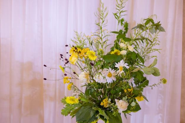 O arco para a cerimônia de casamento decorado com flores de tecido e folhagens fica em uma floresta de pinheiros