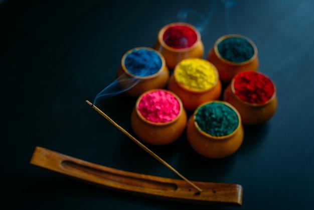 O aroma ardente e fumegante adere ao círculo de pó de holi em copos de barro. cartão feliz holi