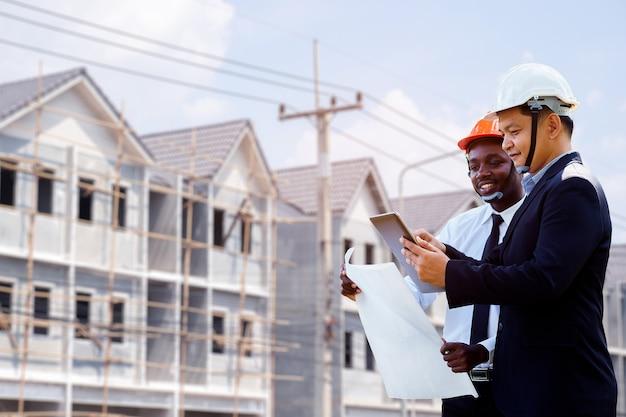 O arquiteto asiático e africano projeta um plano de equipe de dois especialistas com um edifício