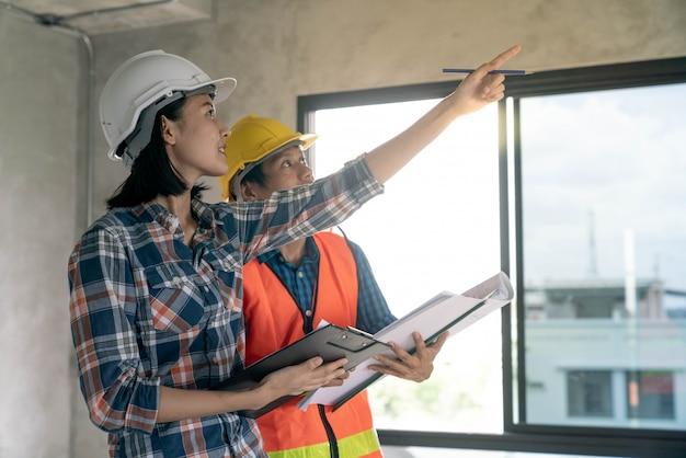 O arquiteto e o inspetor do contramestre defeituam o edifício home do trabalho antes do projeto completo