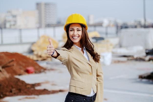 O arquiteto fêmea caucasiano lindo vestiu ocasional esperto e com o capacete amarelo que está no canteiro de obras e que dá os polegares acima.
