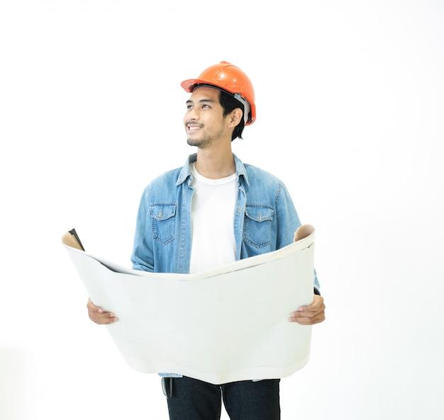 O arquiteto jovem asiático em jeans casuais usa capacete de cor laranja, olhando para longe com cara feliz e sorriso