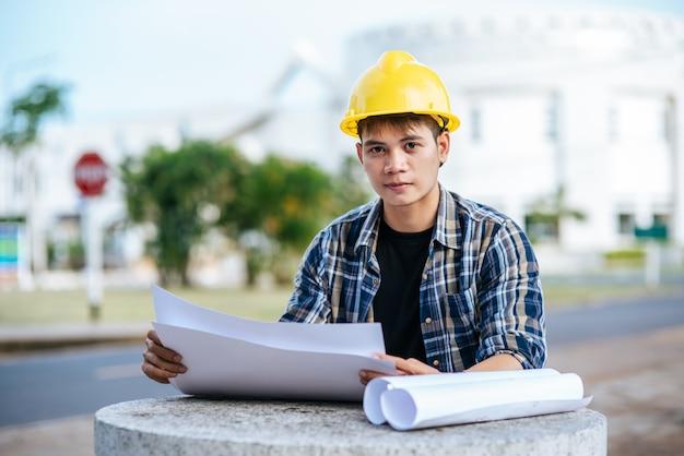 O arquiteto sentou e inspecionou o plano de construção.