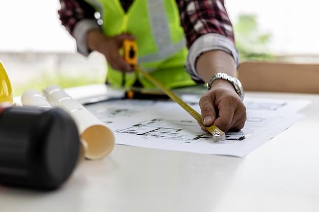 O arquiteto usa uma fita métrica para medir os projetos da casa, ele verifica as plantas que ele fez antes de enviar para os clientes, ele projeta a casa e o interior.