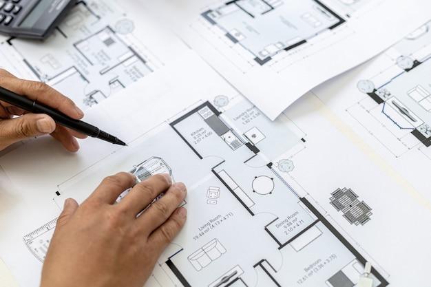 O arquiteto verifica as plantas que projetou, está verificando a exatidão e corrigindo os projetos da casa antes de apresentá-los ao cliente. idéias de design e design de interiores.