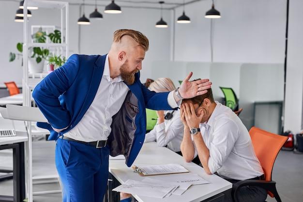O arrogante diretor da empresa repreende o homem por mau trabalho, indo despedi-lo do trabalho. no escritório, diretor barbudo aponta para a porta, funcionário está chorando