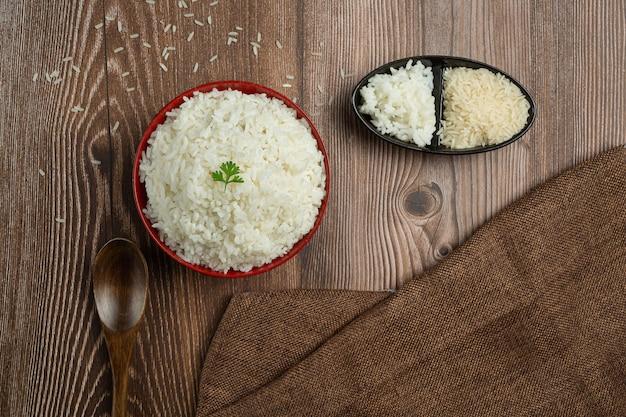 O arroz branco é colocado em uma xícara no chão de madeira.