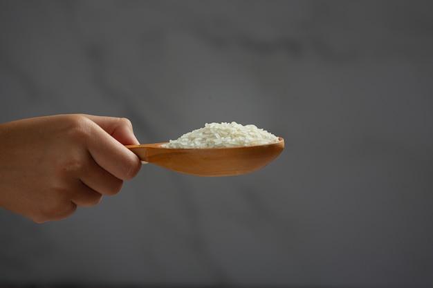 O arroz branco é segurado em uma colher pela mão que segura a colher.