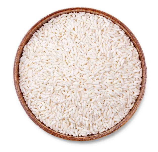 O arroz branco em uma tigela de madeira isolado no fundo branco com traçado de recorte