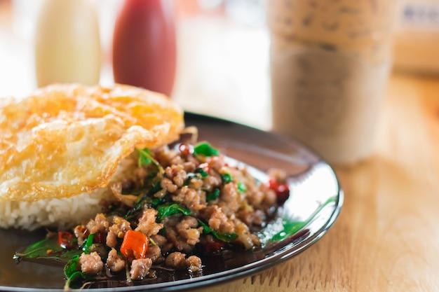 O arroz cobriu com carne de porco salteado e manjericão e ovo frito, copo dos pimentões e molho de peixes.