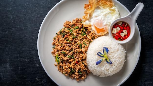 O arroz cobriu com carne de porco salteado e manjericão em de madeira. comida tailandesa