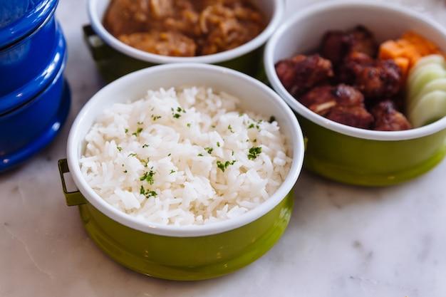 O arroz cozinhado com salsa serviu no portador de aço do alimento.