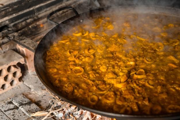 O arroz em ponto na paella valenciana com brasas e legumes