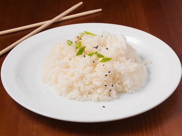 O arroz saboroso é guarnecido com cebolinha e sementes de gergelim em um prato branco