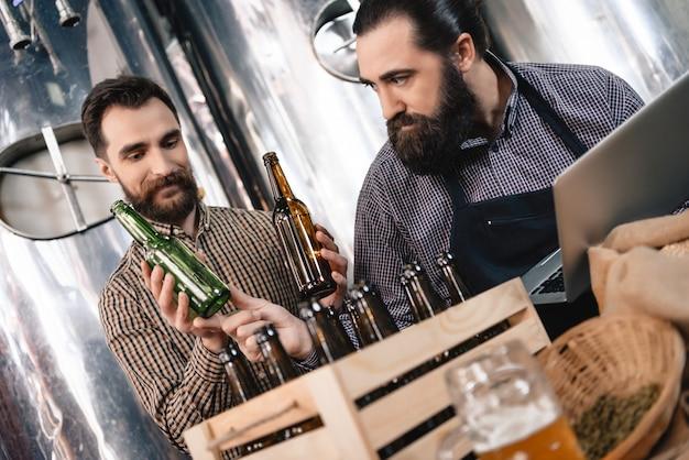 O artesão atento escolhe a cervejaria das garrafas de cerveja.