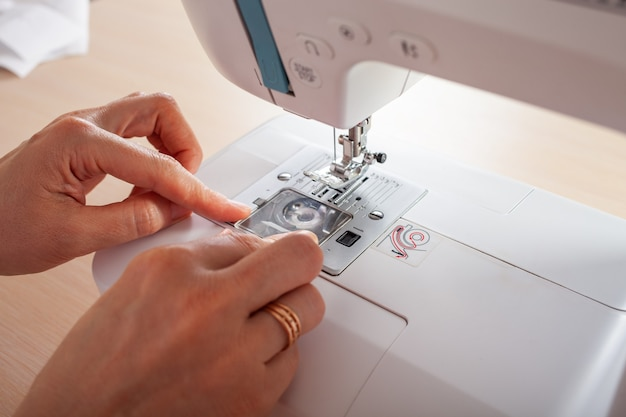 O artesão costureira enche a linha no carretel inferior da máquina de costura automática