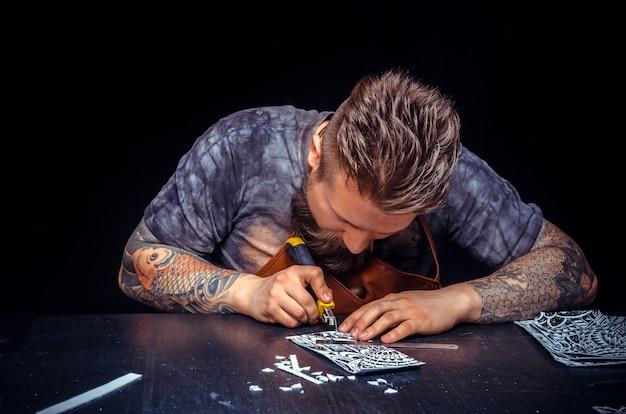 O artesão de couro processa uma peça de couro