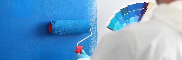 O artesão segura o rolo e uma paleta de cores e pinta a parede branca de azul. serviços de pintura de parede e conceito de pintura