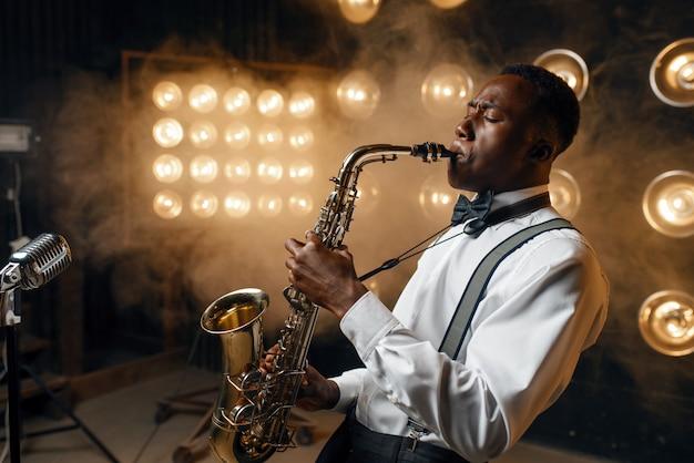 O artista de black jazz toca saxofone no palco