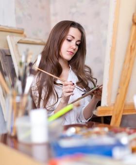 O artista de cabelos longos pinta qualquer coisa na tela