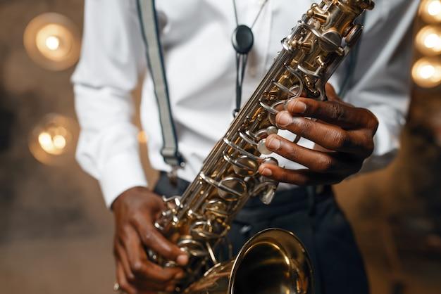 O artista de jazz masculino toca saxofone no palco com holofotes. black jazzman se apresentando na cena