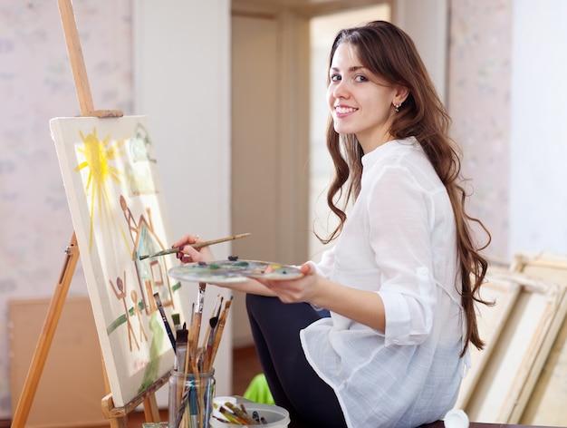 O artista feminino de cabelos compridos pinta a imagem sobre tela
