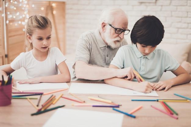 O artista idoso ensina miúdos a desenhar com lápis. de volta à escola