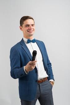 O artista. jovem elegante falando segurando o microfone, isolado em um estúdio.