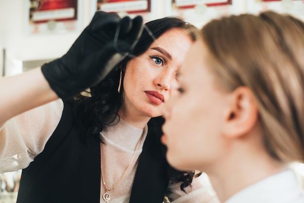 O artista mestre de sobrancelhas corrige as sobrancelhas usando um fio no salão de forma eficaz