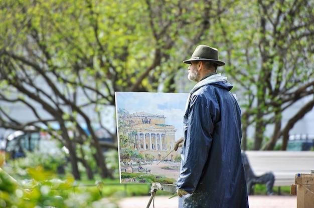 O artista na rua pintando sobre tela