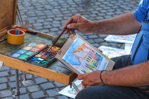 O artista pinta uma foto com tintas coloridas